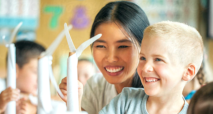 Woman and child smiling looking at a paper arts and crafts windmill