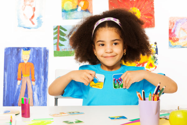 Cute African girl playing developmental game holding cards matching relation by table sitting in playroom with wall behind full of children drawings